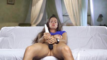 Девушка сидит на диване и дрочит писю вибратором